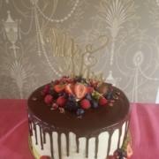Hochzeitstorte im Drip cake Style mit Ganache Beeren und Topper.
