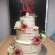 Hochzeitstorte semi naked cake mit Blumendekor und Caketopper.